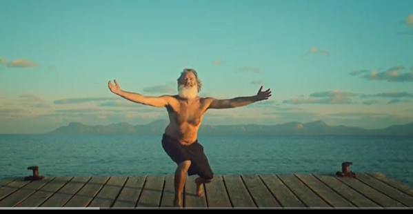 Iggy Pop stands arms wide on a dock with blue sky and ocean in background